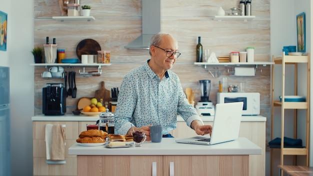 Vie quotidienne d'un homme âgé dans la cuisine pendant le petit-déjeuner à l'aide d'un ordinateur portable tenant une tasse de café. personne âgée à la retraite travaillant à domicile, télétravaillant à l'aide d'une communication en ligne sur internet à distance sur mod