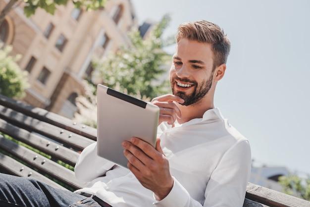 Vie sociale jeune homme souriant assis sur un banc dans le parc tenant sa tablette