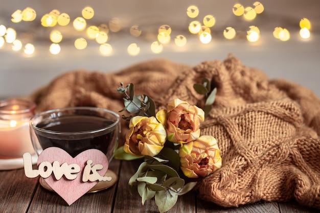 La vie toujours festive l'aime avec un verre dans une tasse, des fleurs et des détails de décoration sur une surface en bois