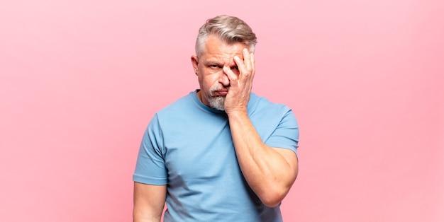 Vieil homme âgé s'ennuyant, frustré et somnolent après une tâche fastidieuse, ennuyeuse et fastidieuse, tenant le visage avec la main
