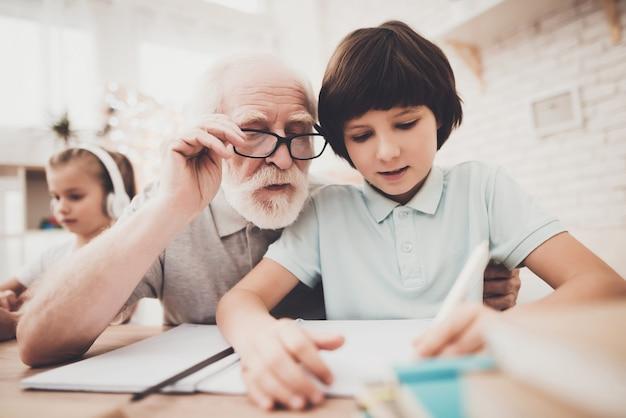Un vieil homme aide un enfant qui apprend dur à faire ses devoirs.