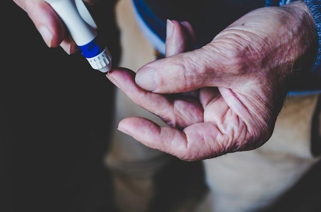 Vieil homme à l'aide d'un stylo lancette sur fond noir
