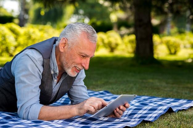 Vieil homme à l'aide d'une tablette à la nature