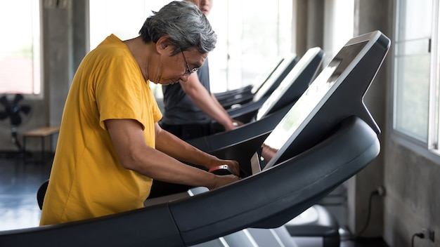 Vieil homme asiatique des années 60 aux cheveux gris à pied sur des tapis roulants dans une salle de sport.