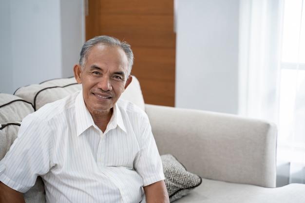 Vieil homme asiatique assis sur le canapé avec un sourire en regardant la caméra