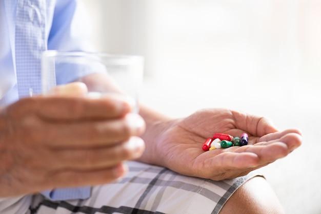 Vieil homme asiatique prenant en pilule et une autre main tenant un verre d'eau minérale propre