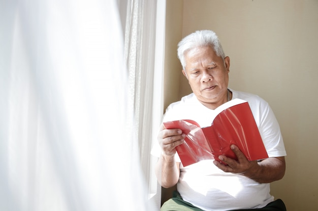 Un vieil homme asiatique s'assied à côté de la fenêtre