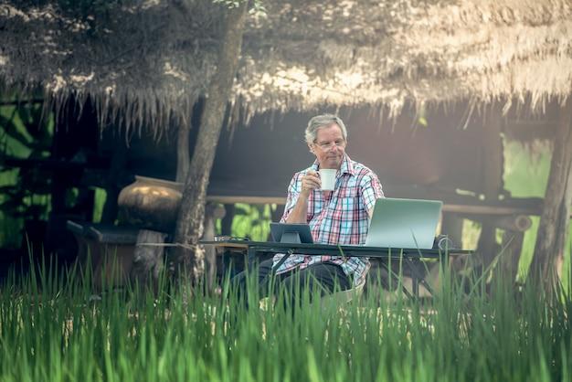 Vieil homme assis à un bureau en plein air à l'aide d'un ordinateur portable