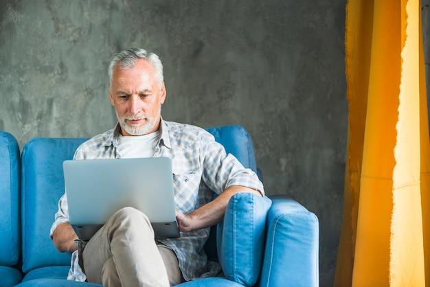 Vieil homme assis sur un canapé bleu en utilisant un ordinateur portable