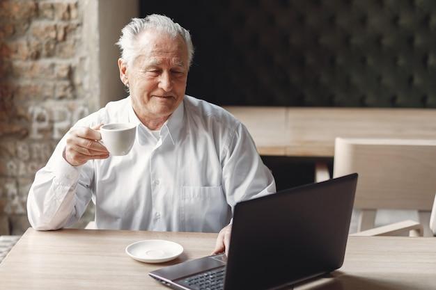 Vieil homme assis à la table et travaillant avec un ordinateur portable