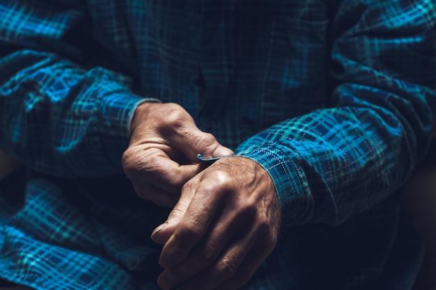 Le vieil homme attache un bouton sur la manche de sa chemise