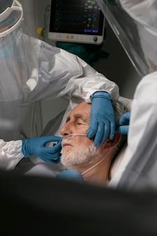 Vieil homme au lit d'hôpital ayant besoin d'un respirateur