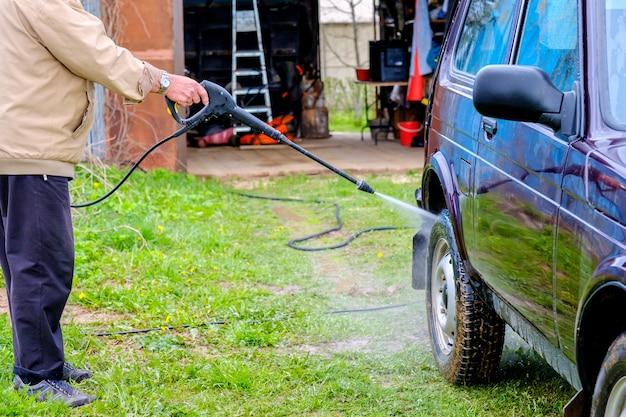 Un vieil homme aux cheveux gris lave une voiture à l'extérieur avec un appareil à haute pression