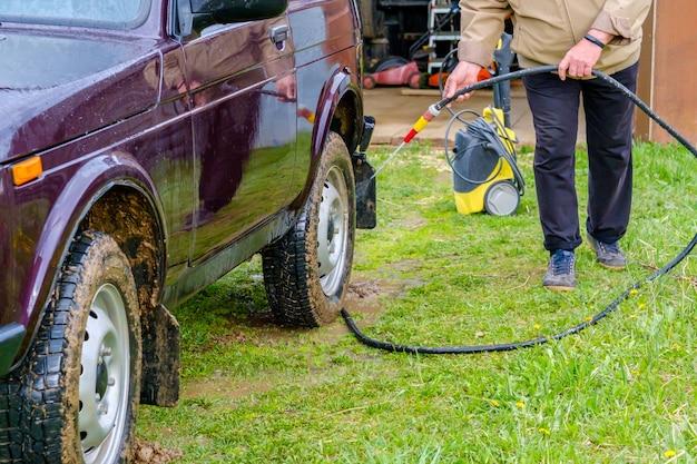 Un vieil homme aux cheveux gris lave une voiture à l'extérieur avec un tuyau d'arrosage