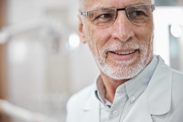 Vieil homme barbu portant des lunettes et une blouse de laboratoire souriant tout en regardant loin de la caméra