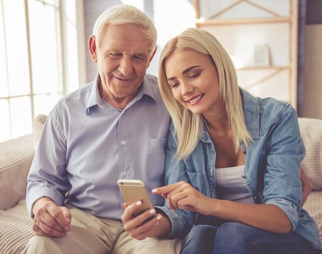 Vieil homme et belle jeune fille utilisent un smartphone.