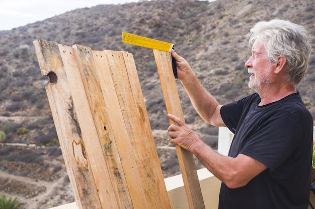 Vieil homme caucasien senior travaillant à la maison construisant une table avec du bois de palette recyclé. prendre des mesures avec du matériel. travail en plein air, concept de style de vie à la retraite