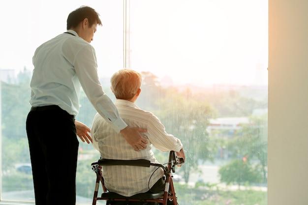 Vieil homme sur une chaise roulante et médecin à l'hôpital santé et concept médical pour comercial