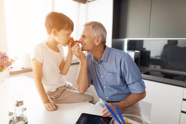 Vieil homme en chemise bleue et son petit-fils qui est assis à côté de lui.
