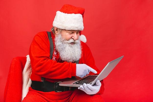Vieil homme en costume de père noël tenant un ordinateur portable isolé sur fond rouge