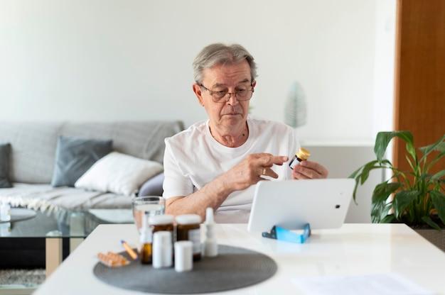 Vieil homme de coup moyen parlant au docteur en ligne