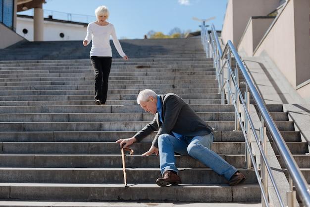 Vieil homme craintif à la mode transférant la douleur dans le corps et se tenant debout tandis que la femme polie descend vers lui