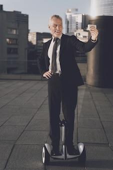 Le vieil homme dans un costume strict fait selfie