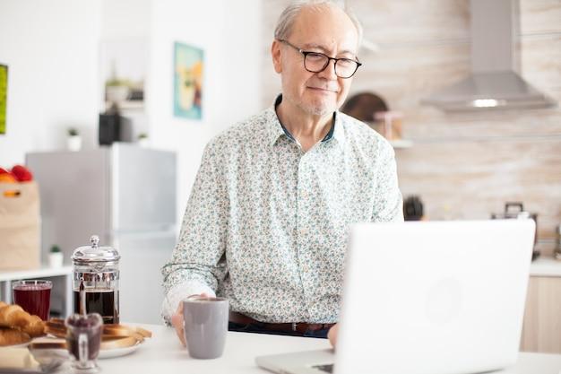 Vieil homme dans la cuisine travaillant à distance. vie quotidienne d'un homme âgé dans la cuisine pendant le petit-déjeuner à l'aide d'un ordinateur portable tenant une tasse de café. personne âgée retraitée travaillant à domicile, télétravaillant à distance