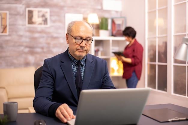 Vieil homme dans la soixantaine travaillant sur un ordinateur portable dans un salon confortable tandis que sa femme est en arrière-plan