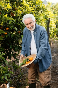 Vieil homme debout à côté de ses orangers à l'extérieur