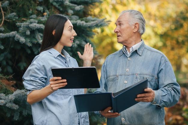 Vieil homme debout dans un parc avec sa petite-fille
