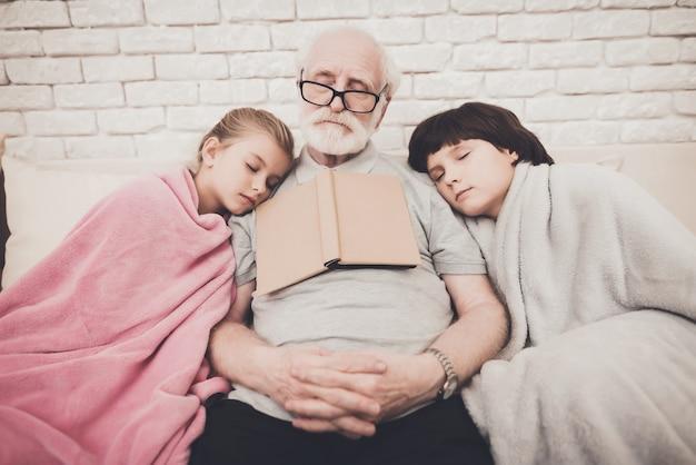 Vieil homme et deux petits-enfants sont tombés endormis avec un livre.