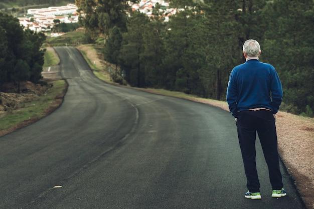 Vieil homme de dos debout sur une route isolée