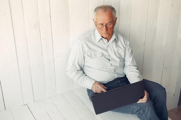 Vieil homme élégant assis à la maison et à l'aide d'un ordinateur portable