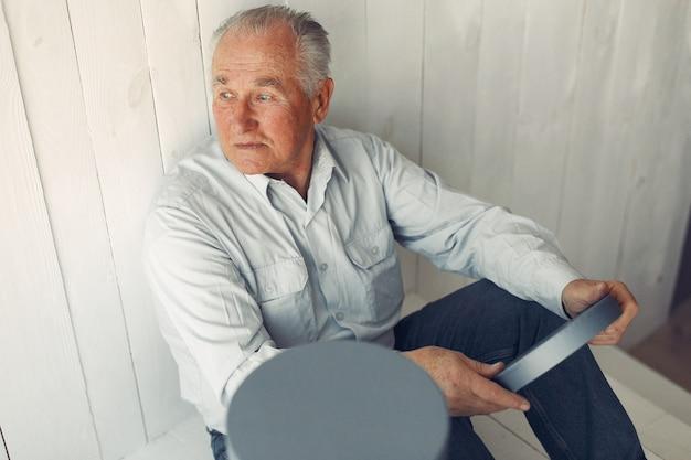 Vieil homme élégant assis à la maison avec des cadeaux de noël