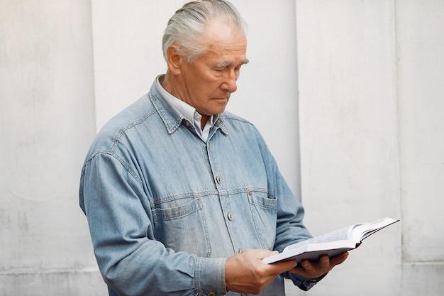 Vieil homme élégant debout avec un livre