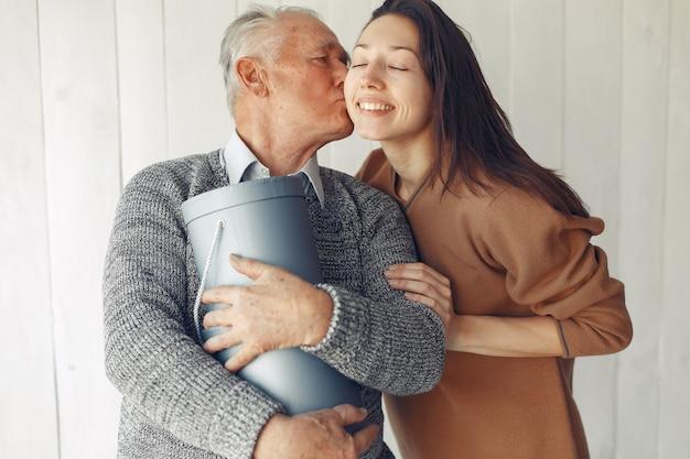 Vieil homme élégant debout à la maison avec sa petite-fille