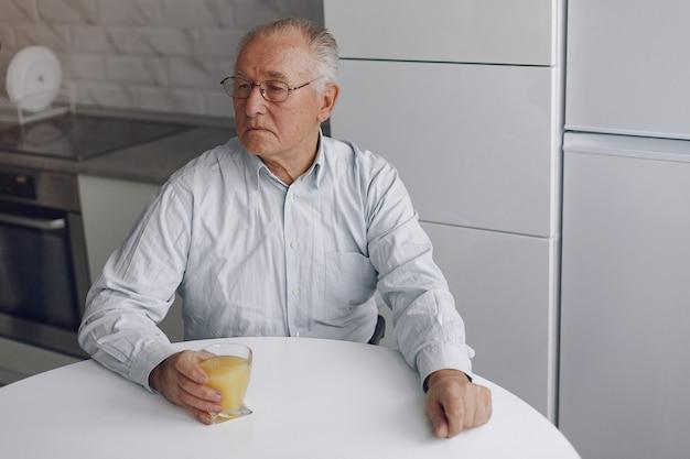 Vieil homme élégant à la maison avec du jus d'orange