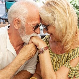 Vieil homme embrassant la main de la femme