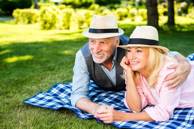 Vieil homme embrassant sa femme sur une couverture