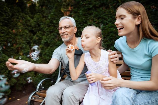 Un vieil homme est assis sur un banc avec des filles.