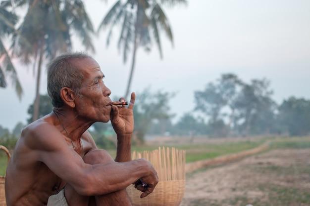 Vieil homme était assis fumée