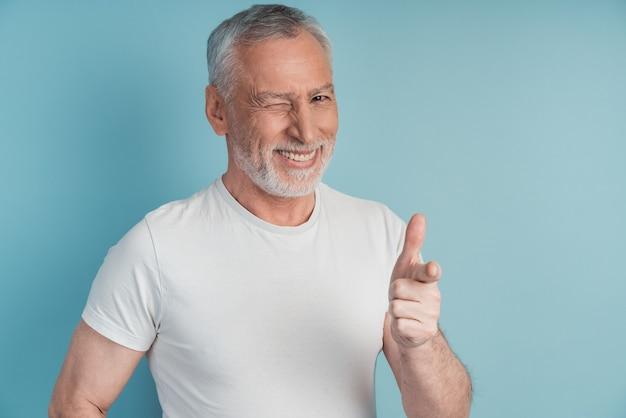 Le vieil homme fait un clin d'œil et montre du doigt avec son index.