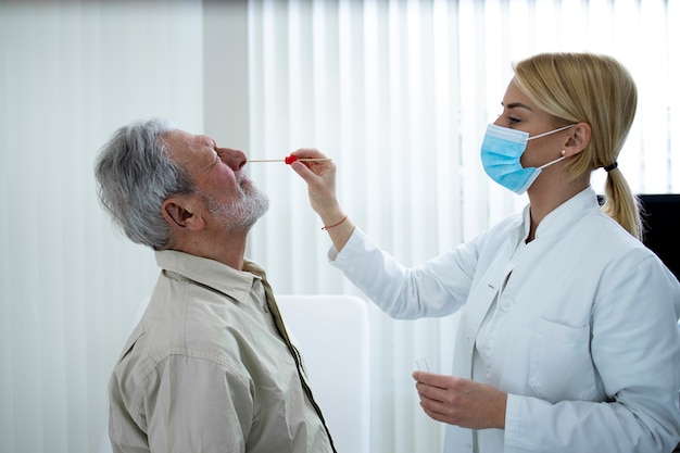 Un vieil homme fait un test de pcr au bureau du médecin pendant l'épidémie de virus corona