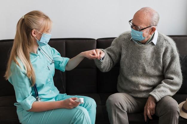 Vieil homme fist bumping infirmière dans une maison de soins infirmiers