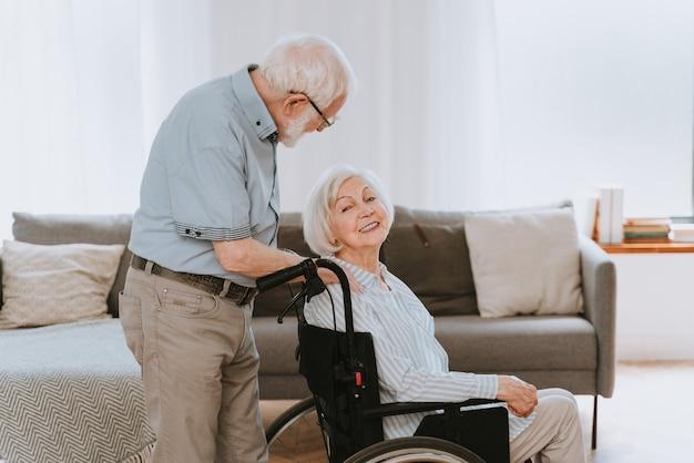 Vieil homme handicapé en fauteuil roulant couple de personnes âgées à la maison partenaire revenant de l'hôpital