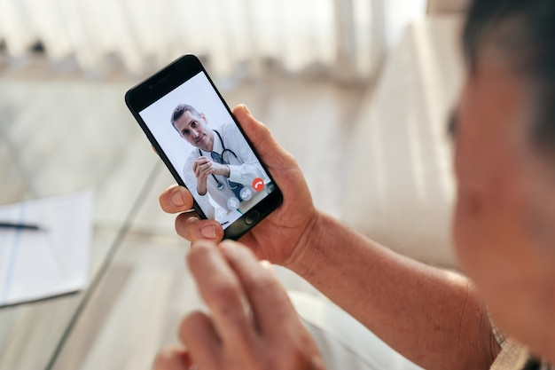 Un vieil homme heureux rencontre son médecin via un appel vidéo par téléphone intelligent à la maison, pendant que le covid-19 sort.