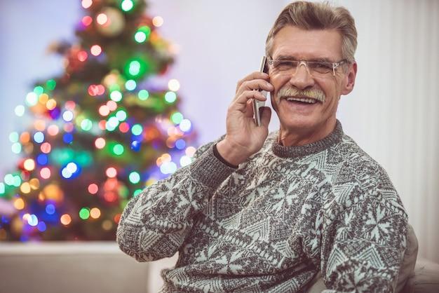 Le vieil homme heureux téléphone près de l'arbre de noël