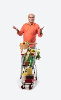Vieil homme indien avec caddie ou chariot plein de légumes, de fruits et d'épicerie