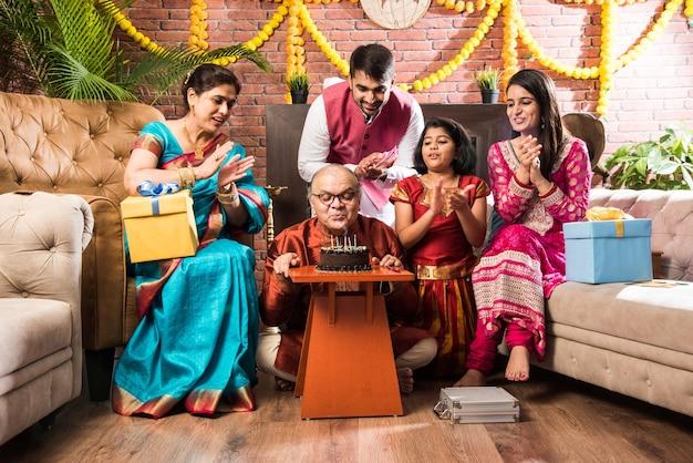 Vieil homme indien avec la famille célébrant l'anniversaire en soufflant des bougies sur le gâteau tout en portant des vêtements ethniques